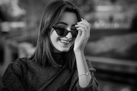 beautiful happy luxury young woman with sunglasses in sunny autumn park laughing, monochrome