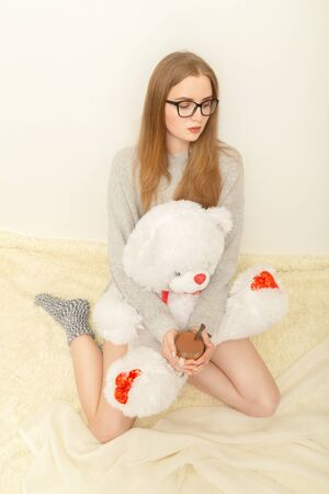 young woman sitting on white fur with mug of tea hugs teddy bear