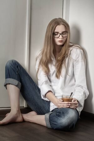 sad young blond woman in eyeglasses sitting on floor looking down