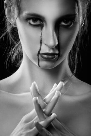young woman with bare shoulders and Halloween bloody makeup looking at camera. studio shot. monochrome Stok Fotoğraf