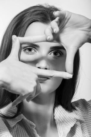 fun woman looking at camera through fingers square smiling
