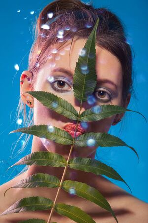 fun young woman cover her face with tropical leaf looking at camera blue background, making grimace Stockfoto
