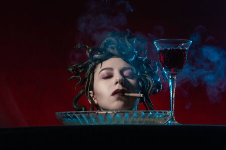 chopped off head of medusa gorgon with closed eyes on dish smoking cigarette, red background Imagens
