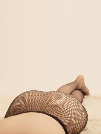beautiful female buttocks in fishnet tights, unrecognizable woman lying on fur, background with copy space