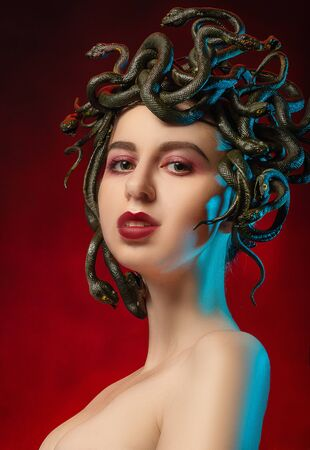 medusa gorgon with bare shoulders looking at camera on red background Imagens