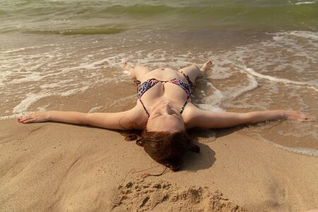single happy pregnant young red hair woman in bikini lying at sea surf