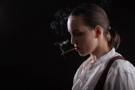 serious young woman smoking cigarette on black background