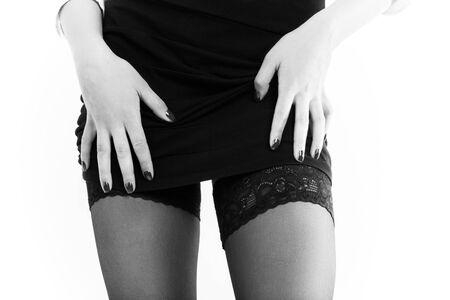 mujer joven mueve la falda hacia arriba, muestra sus hermosas caderas delgadas en medias. Acercamiento aislado sobre fondo blanco, monocromo