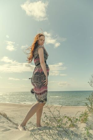 young red hair woman in dress standing on sand dunes, sunbathes, looking at camera Stock fotó