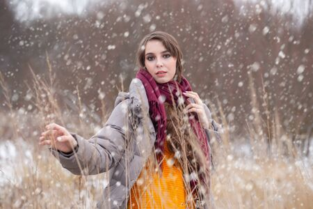 freezing young woman on winter meadow under falling snow