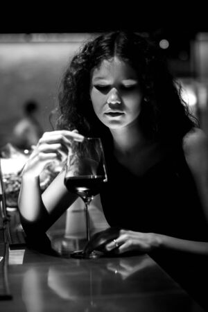 single luxury beautiful woman with wine sitting in restaurant bar, monochrome