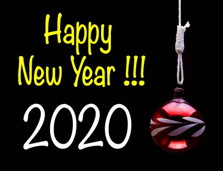hung christmas ball on the dark background with greetings text on 2020 year