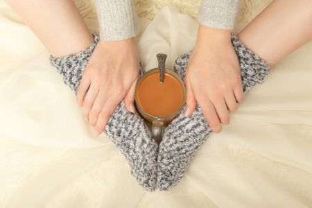 unrecognizable young woman in sweater and woolen socks with cup of hot tea, closeup hands and feet, monochrome