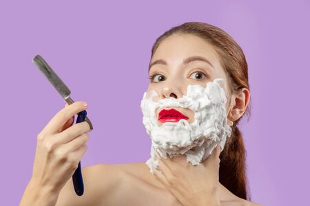 fun young woman has shave with open razor on violet background, looking at camera