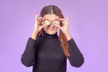 happy red hair young woman with sushi on violet background cover her eyes