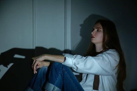 Triste joven sentada en la oscuridad en la esquina mirando hacia adelante vista de perfil