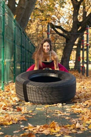 young sports woman does gymnastics on the autumn sports ground