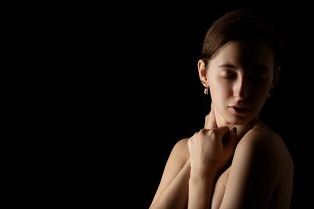 sensual topless young aroused woman on black background with copy space