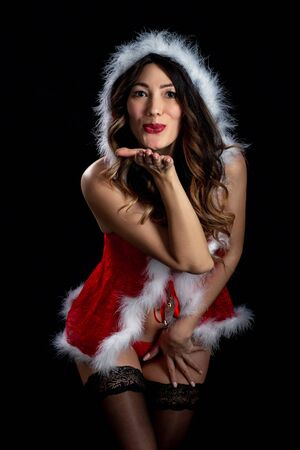 sensual young woman in miss santa costume on black background send kiss, looking at camera 免版税图像