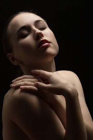 sensual topless young aroused woman with closed eyes on black background Standard-Bild