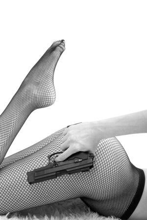 unrecognizable female body in fishnet tights with gun in hand, monochrome