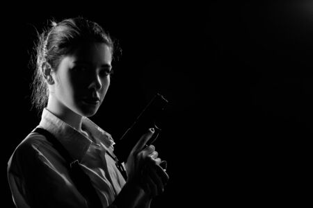 serious young woman with gun in dark looking at camera monochrome image with copy space