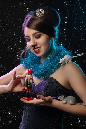 girl in Mouse Queen costume plays with Nutcracker toy on stars background Banque d'images