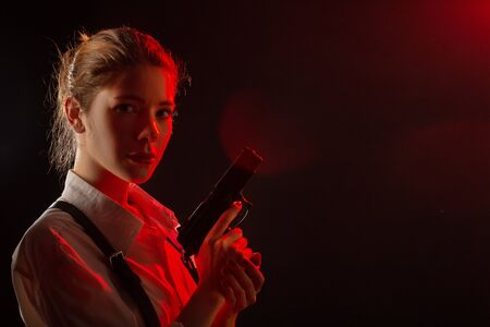 serious young woman with gun in dark looking at camera toned image with copy space