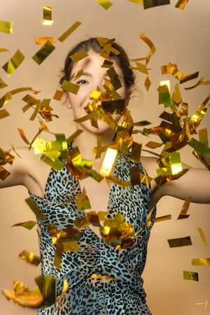 Happy girl on yellow background, golden confetti slowly scatter and fall