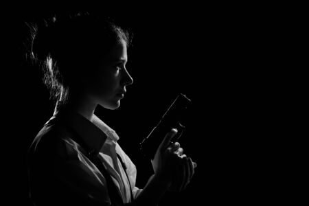 young woman with gun in dark with back light. Profile silhouette view, monochrome