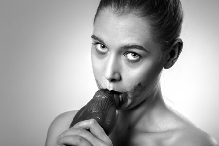 young happy woman with bare shoulders eats chocolate santa claus on white background with copy space looking at camera, monochrome