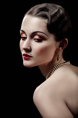 mujer joven de lujo en estilo retro vintage sobre fondo negro Foto de archivo