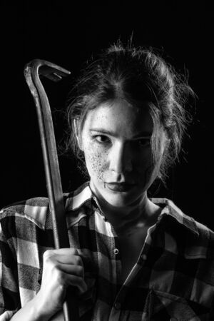 serious young bloody woman with crowbar in dark looking at camera monochrome image