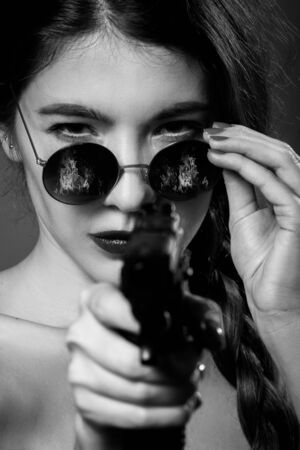 serious young woman with black eyeglasses and gun aiming at camera, closeup portrait, monochrome