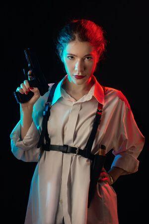 serious young woman with gun in dark looking at camera multicolor image Foto de archivo