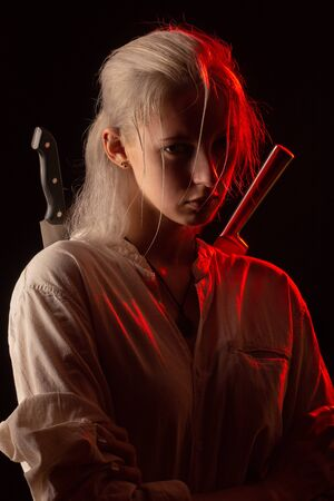 serious young woman with white hair and knives on black background looking at camera