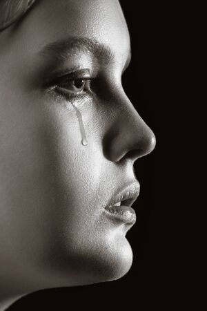 sad woman crying, looking aside on black background, closeup portrait, profile view, monochrome