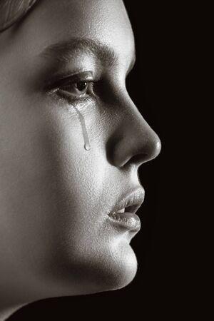 Traurige Frau weint, auf schwarzem Hintergrund beiseite schauend, Nahaufnahmeporträt, Profilansicht, Monochrom