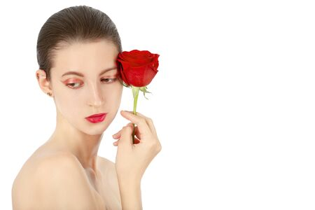 beautiful young woman with red rose, natural beauty makeup and bare shoulders looking aside closeup