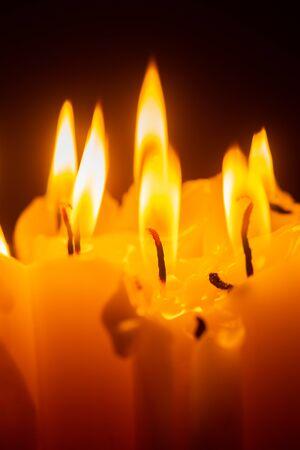 Wachskerzen brennen in der dunklen Detailansicht Standard-Bild