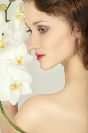 beautiful female face with luxury makeup on white orchids looking aside, profile view