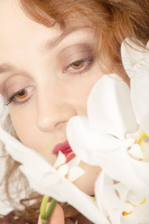 beautiful female face with luxury makeup on white orchids looking down