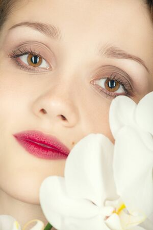 beautiful female face with luxury makeup on white orchids looking at camera