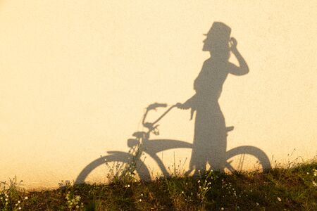 female silhouette with bicycle profile view at yellow concrete wall