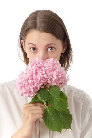 young woman smell pink flower isolated on white background, raise eyebrows looking at camera