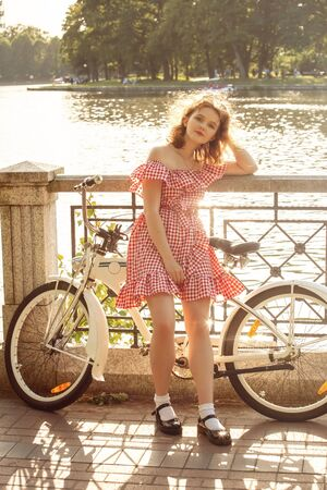 beautiful pinup girl with red dress and curly red hair posing with bike at sunny park in sun light