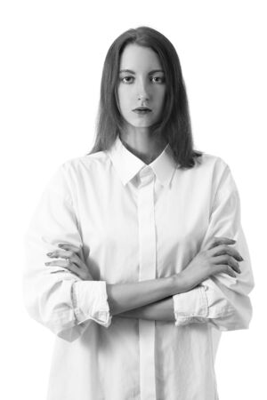 serious young woman with crossed arms in white blouse looks at camera front view on white background, monochrome