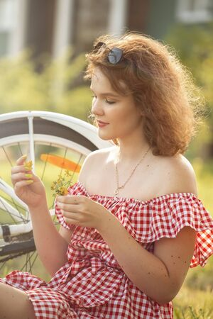 beautiful pinup girl with bare shoulders dress and curly red hair sitting with bike and flowers in sunny park in sun light 免版税图像