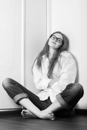 young woman at quarantine sitting on floor looks at camera, monochrome