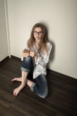 young woman at quarantine sitting on floor with mug of tea looks at camera